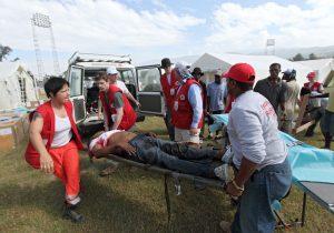 ein verletzter Mann liegt auf einer Trage, die von mehreren Helfern getragen wird