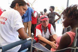 eine Krankenschwester hockt vor vor einer junge Haitianerin, die auf einem Stuhl sitzt